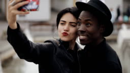 Slowmotion of white woman and black man couple makes selfie video on smartphone. She kiss his cheek. They smiling, laughing together.