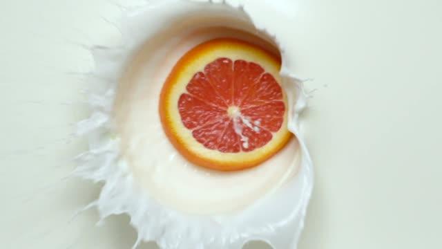 スローモーション: オレンジ色のスライスが牛乳に落ちます。 - 深皿点の映像素材/bロール