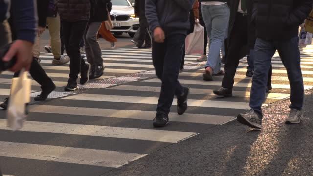 vidéos et rushes de slowmotion - peuples marchant sur un passage pour piétons avec le coucher du soleil brillant - piéton