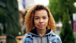 Slowmotion portrait of pretty African American girl modern teenager looking at camera and smiling while standing in beautiful green park. Happy people and city concept.
