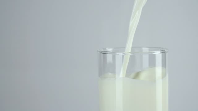 slow-motion: pouring milk into a glass on white background. - soy milk stock videos and b-roll footage