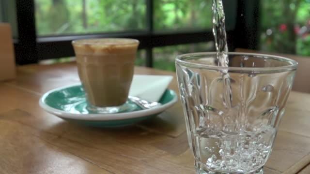 vídeos de stock e filmes b-roll de slow-motion, pouring water into a drinking glass - copo vazio