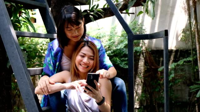 vidéos et rushes de 4k slowmotion: romantique lgbt couple adolescent relaxant et embrassant. ils regardent mobilephone - trans