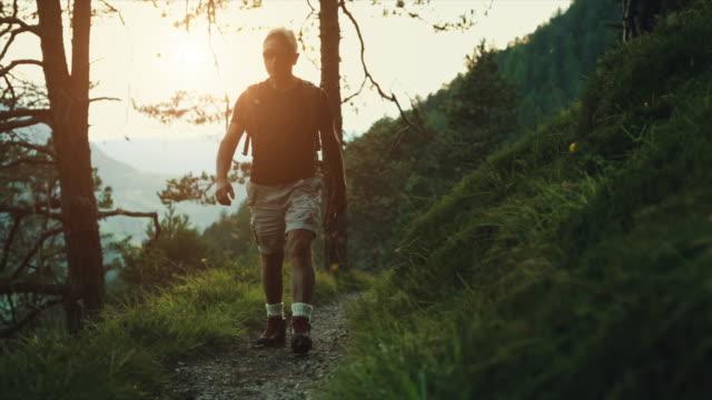 stockvideo's en b-roll-footage met slow-motion senior man trail wandelen in het bos - gespierd