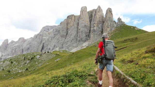 Camino de hombre senior lenta caminata en montaña