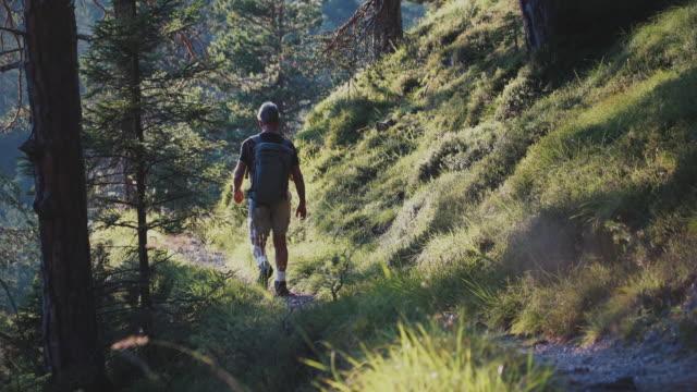 Slow-motion senior man trail hiking on mountain