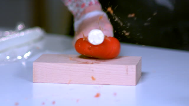 Slow-motion sequence showing a baton being used to smash into tomatoes on a wooden board.