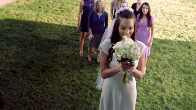 slow-motion shot of a bride throwing a bouquet of flowers. - bouquet video stock e b–roll