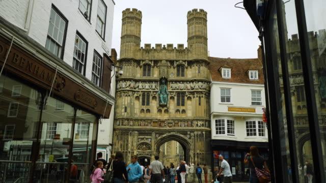 stockvideo's en b-roll-footage met slow-motion shot of people walking around canterbury's christ church gateway, kent, uk. - establishing shot