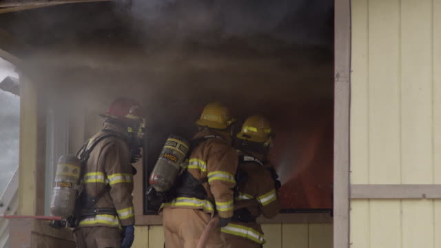 Slow-motion shot of three firemen on the porch of a house spraying water through a window