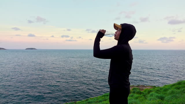 slowmotion shot woman drinking water after run - water bottle stock videos & royalty-free footage