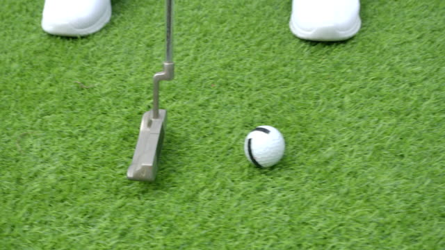 slow-motion shot : women putt the golf ball - golf swing women stock videos & royalty-free footage