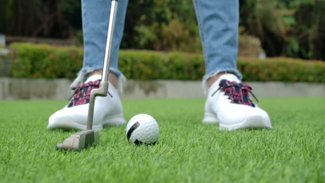 slow-motion shot : women putt the golf ball - golfer stock videos & royalty-free footage