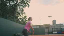 slow-motion side view of a young athlete trains the serve of the tennis ball. A teenage athlete is playing tennis on a court. An active girl is powerfully hitting a ball during sport practicing