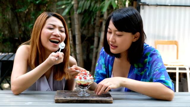 4k スローモーション: 十代の友人は、夏の時間に食べるケーキを楽しみます。時間をリラックスして受け入れます。 - china east asia点の映像素材/bロール