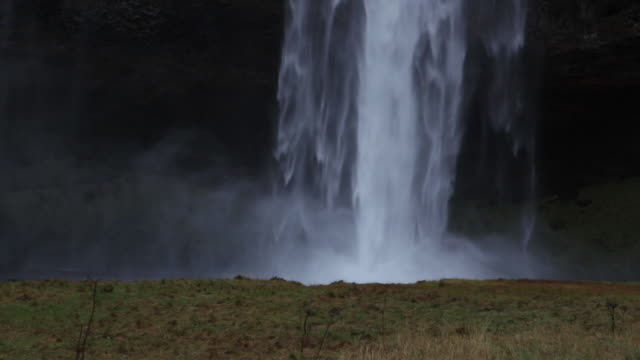 Slow-motion tilt of water tumbling over a craggy rock face and down the long, thin waterfall Seljalandsfoss, before culminating in rolling spray, Iceland.