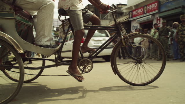 slow-motion, tracking crane shot of a rickshaw as it turns a corner in guwahati in assam, india. - rickshaw stock videos and b-roll footage