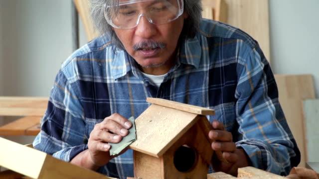 vídeos de stock, filmes e b-roll de slowmotion vista: masculino carpinteiro blowinng madeira para fora depois de lixar uma casa de pássaros na oficina - só um homem maduro