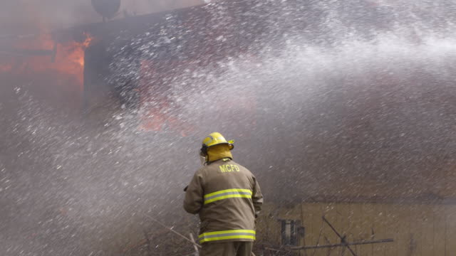 slow-motion view of a fireman with a hose walking toward a burning house while water droplets pour in from right of frame - myrtle creek stock videos and b-roll footage