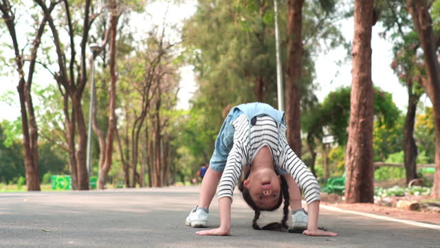slow-motion view of a southeast asian teenage girl in the park tries to do anding in bridge pose, bending over backward on the footpath with feeling positive emotion and happiness of smiling. cheerful child playing at weekend activities. - bending over stock videos & royalty-free footage
