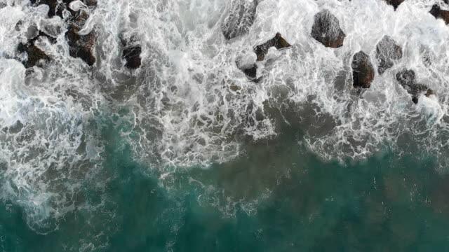 zeitlupen-wellen über felsiges meer - seitenansicht stock-videos und b-roll-filmmaterial