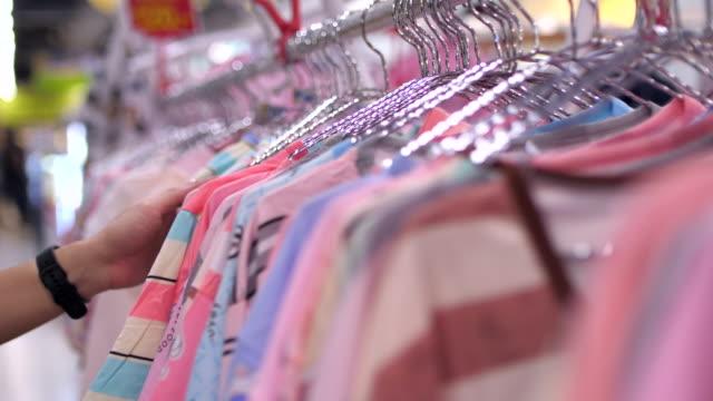 Slowmotion:Closeup woman's hands clothes rack