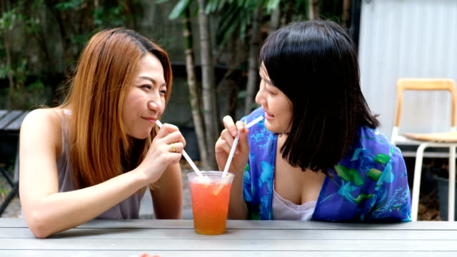 4k slowmotion:romantic lgbt teenage couple drinking fruit juice from same glass in summer time. relaxing and embracing time. - fruit juice stock videos & royalty-free footage