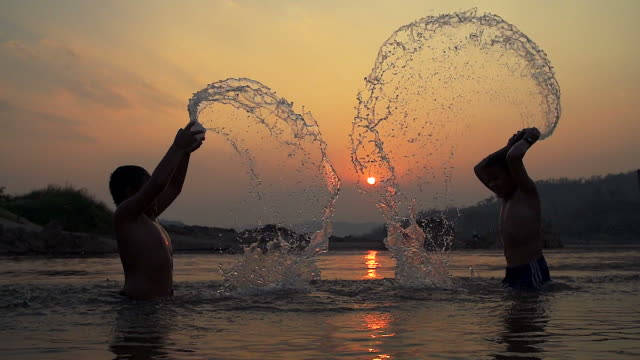 HD Slowmotion:Silhouette happy child splashing played in pond at sunset.