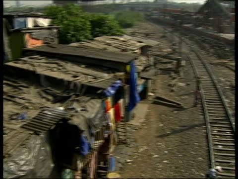 slum shacks beside railroad tracks / mumbai india - アナモルフィック点の映像素材/bロール