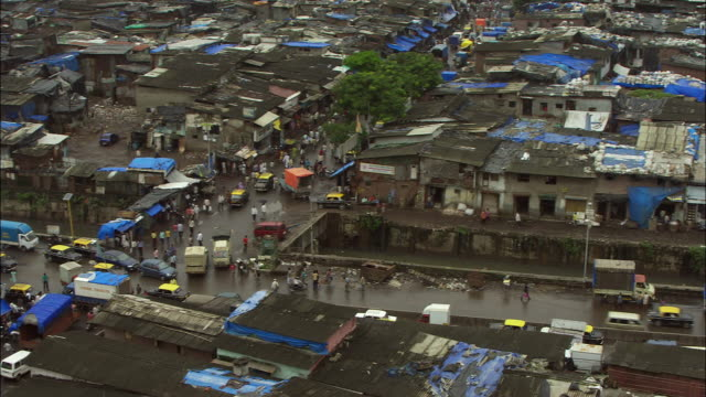 A slum surrounds a busy Mumbai intersection. Available in HD.