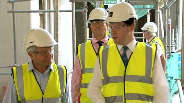 gdp slumps as uk recession deepens north london osborne being shown round construction site - ファイサル・イスラム点の映像素材/bロール