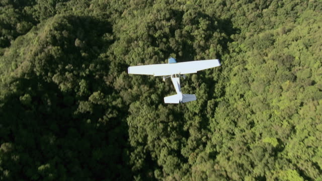 aerial small aircraft flying over tree-covered ridges / hawaii, united states - プロペラ機点の映像素材/bロール