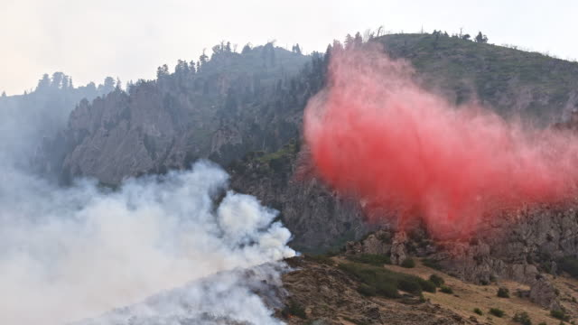 vídeos y material grabado en eventos de stock de small airplane dropping fire retardant on wildfire burning on mountainside - provo