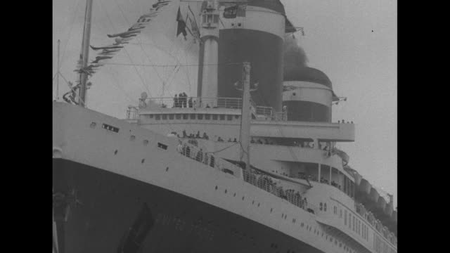 small airplane flies above and past the ss united states in harbor / ls the ss united states in background as people on beach and on road in... - 客船点の映像素材/bロール