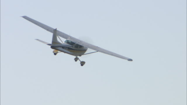 a small airplane flies in a pale blue sky. - propeller aeroplane stock videos & royalty-free footage