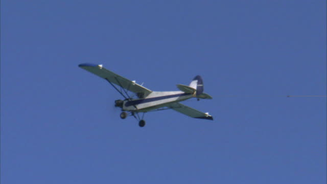 ws la ts small airplane flying against clear sky / miami, florida, usa - プロペラ機点の映像素材/bロール
