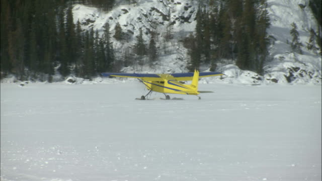 a small airplane lands on frozen tagish lake in the yukon territory. - whitehorse stock videos and b-roll footage