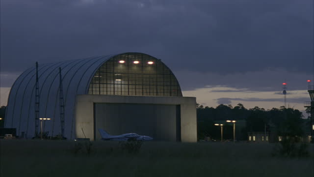a small airplane sits in front of a well-lit hangar. - airplane hangar stock videos & royalty-free footage
