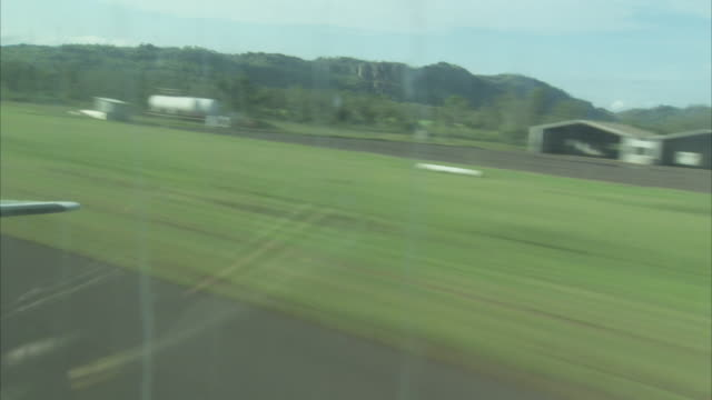 A small airplane takes off from a small runway.