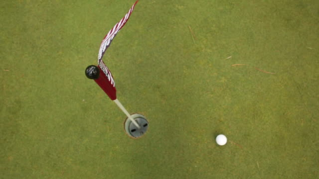 a small american flag blowing in the wind on a putting green. - golf flag stock videos and b-roll footage