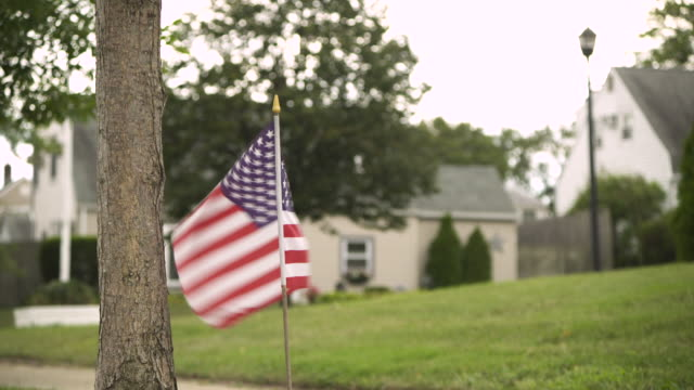 A small American flag near a lawn and houses waves fiercely in a breeze, Levittown, Long Island, USA.
