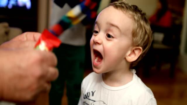 stockvideo's en b-roll-footage met kleine babyjongen met gelukkig gezicht in huis dat banaan gevormde chocoladecake eet - one baby boy only