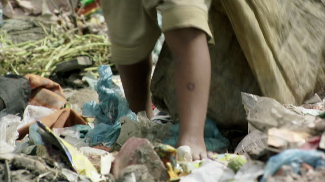 Small, bare-footed children scour piles of rubbish in order to find recyclable materials in Dhaka, Bangladesh.