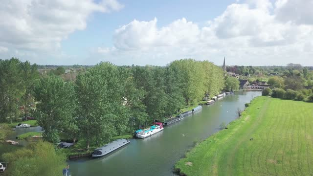 small barge and boats moored on the river thames in abingdon town near oxford city, uk, with lush green trees and grass. - aerial drone shot - barge stock videos & royalty-free footage