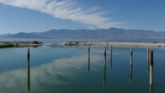 4k small bay on the salton sea pan left puffy clouds on a pale blue sky reflecting in the still water - faglia di sant'andrea video stock e b–roll
