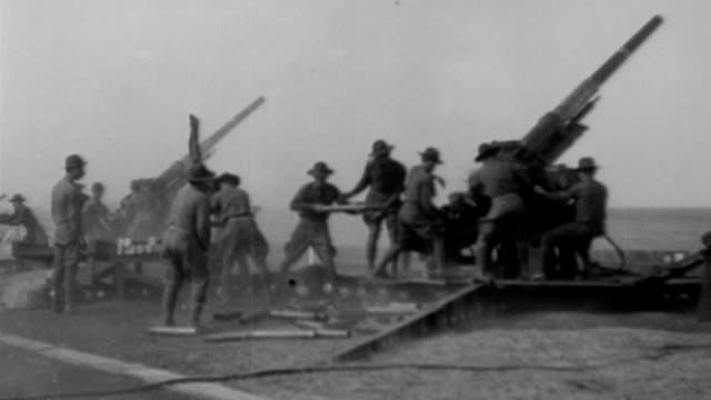 / small biplane flying / coastal guns aimed at sky / projectile floats in air / war secretary patrick j hurley and others point and watch the... - 1932 stock-videos und b-roll-filmmaterial