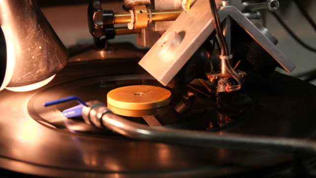 a small black vinyl disc rotates slowly on a carving turntable - electrical equipment stock videos & royalty-free footage
