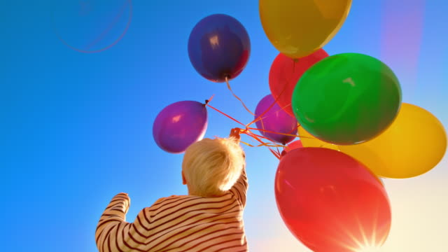 slo mo small blonde boy jumping and releasing a bunch of colourful balloons into the sky - releasing stock videos & royalty-free footage