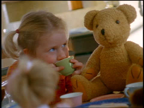 small blonde girl drinking from teacup at tea party with dolls + teddy bear - tea party stock videos and b-roll footage