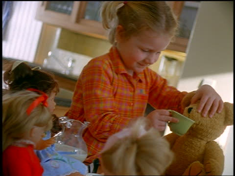 vídeos de stock, filmes e b-roll de small blonde girl feeding teddy bear tea + cookie at tea party with dolls + teddy bears - alimentando